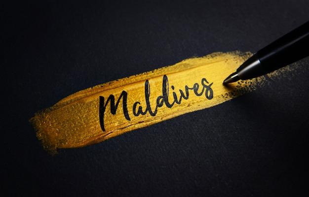 Texto de escritura de maldivas en el pincel de pintura dorada