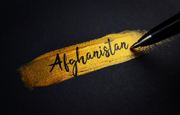 Texto de escritura a mano de afganistán sobre el pincel de pintura dorada