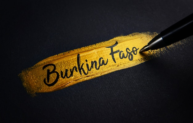 Texto de escritura a mano de burkina faso en pincelada dorada