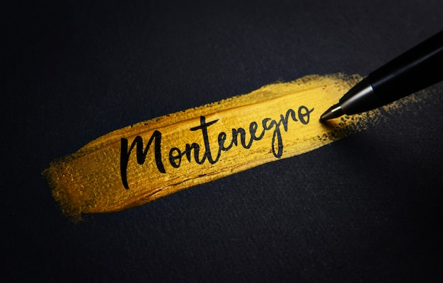 Texto de escritura de montenegro sobre el pincel de pintura dorada