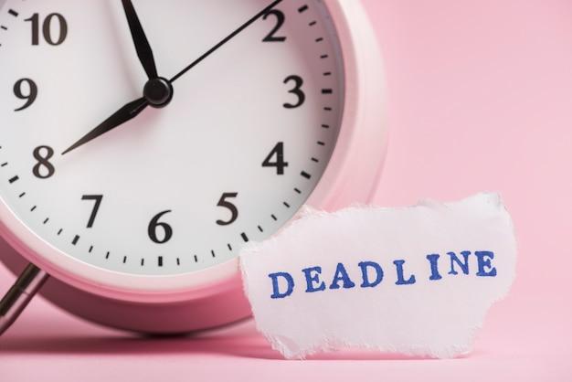Texto de fecha límite en papel rasgado cerca del reloj sobre fondo rosa
