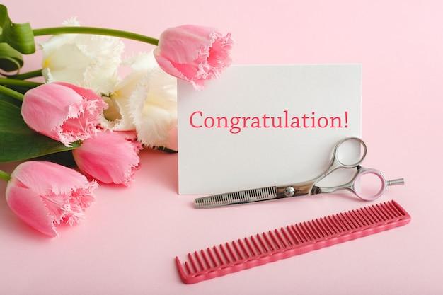 Texto de felicitación en la tarjeta de peluquería, salón de belleza. servicios de belleza. tarjeta blanca en blanco con espacio para texto, maqueta, peine de tijeras de peluquería en ramo de tulipanes rosas sobre fondo rosa.