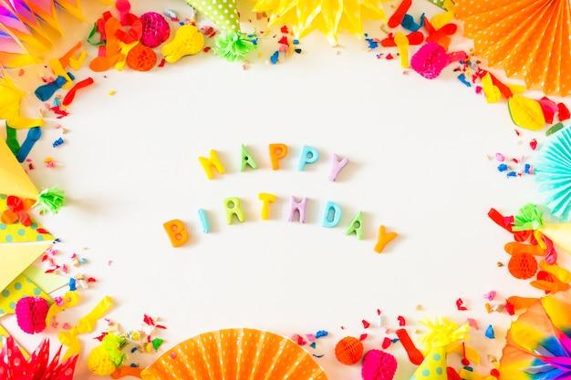 Texto de feliz cumpleaños con accesorios de fiesta sobre fondo blanco