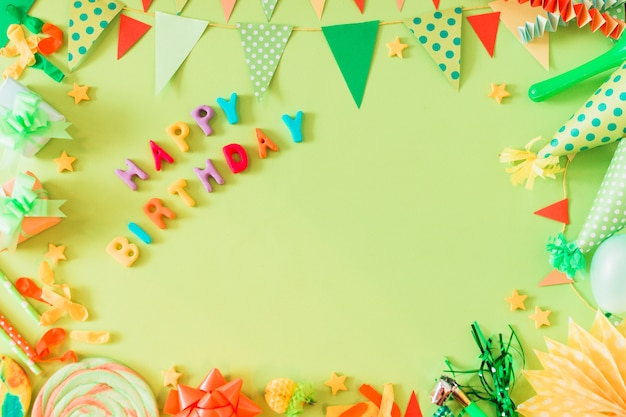 Texto de feliz cumpleaños con accesorios sobre fondo verde