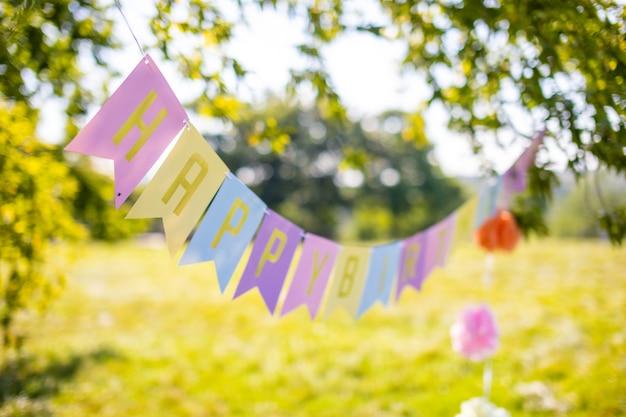 Texto feliz cumpleaños en coloridas banderas de papel en el parque