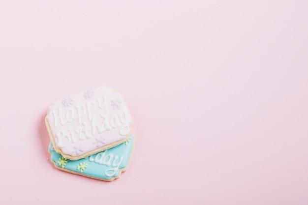 Texto de feliz cumpleaños en galletas frescas sobre fondo rosa