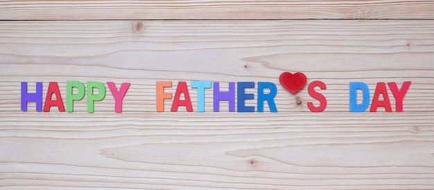Texto feliz del día de padre con forma roja del corazón en fondo de madera.