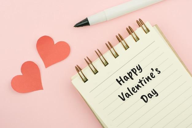 Texto feliz del día de tarjetas del día de san valentín escrito en un cuaderno con la pluma