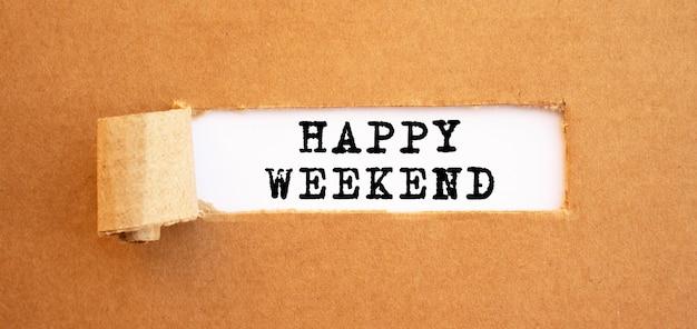 Texto feliz fin de semana que aparece detrás de papel marrón rasgado