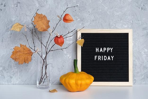 Texto de feliz viernes en pizarra negra y ramo de ramas