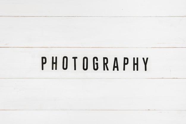 Texto de fotografía negro sobre mesa de madera blanca