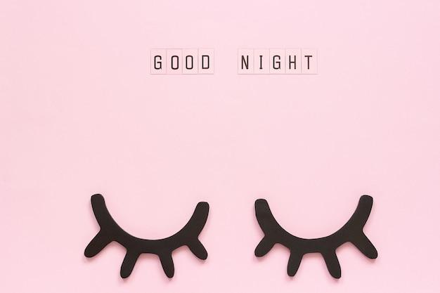 Texto good night y pestañas negras de madera decorativas, ojos cerrados sobre fondo de papel rosa.