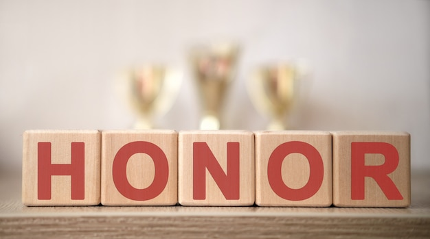 El texto del honor en cubos de madera, en el fondo de las copas