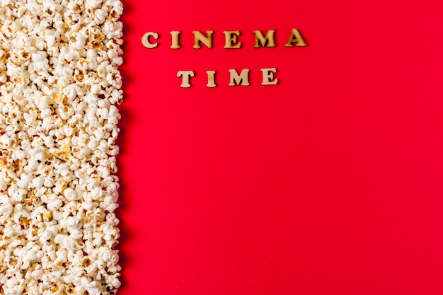 Texto de la hora del cine cerca de las palomitas de maíz sobre fondo rojo