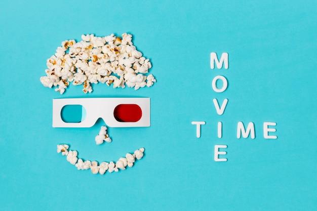 Texto de la hora de la película con cara antropomorfa sonriente hecha con palomitas de maíz y gafas 3d