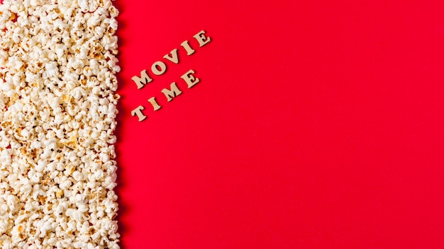 Texto de la hora de la película cerca de las palomitas de maíz sobre fondo rojo