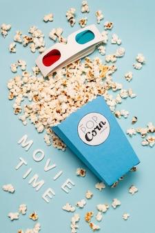 Texto de la hora de la película con palomitas de maíz derramadas de palomitas de maíz y gafas 3d sobre fondo azul