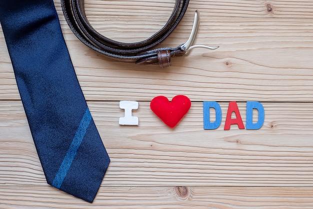 El texto i love dad con corbatas azules, cinturón y forma de corazón rojo sobre madera