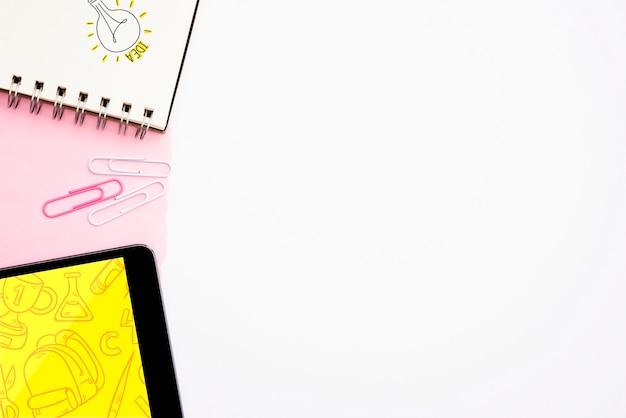 Texto de idea y bombilla dibujada a mano en bloc de notas en espiral con tableta digital sobre fondo blanco.