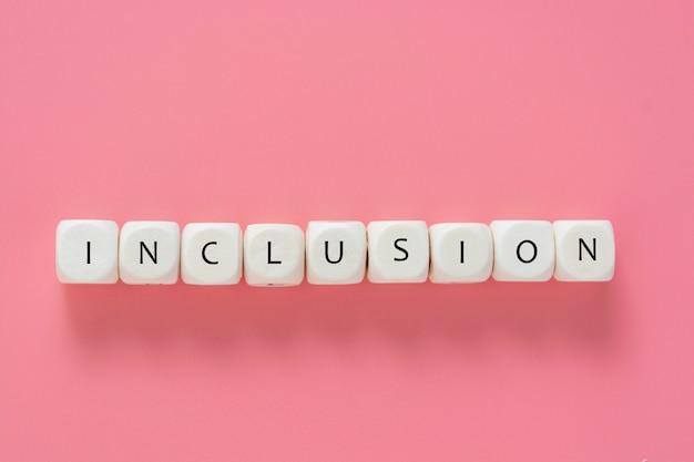 Texto de inclusión de cubos de madera en mesa rosa. concepto social inclusivo. endecha plana.