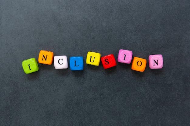 Texto de inclusión de cubos multicolores sobre fondo oscuro. concepto social inclusivo.