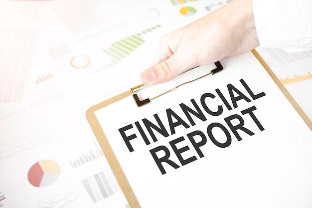 Texto informe financiero en plato de papel blanco en manos de empresario con diagrama financiero. concepto de negocio