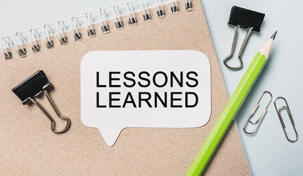 Texto lecciones aprendidas en una pegatina blanca con espacio para material de oficina
