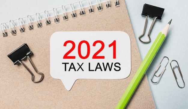 Texto de las leyes fiscales de 2021 en una pegatina blanca con material de oficina