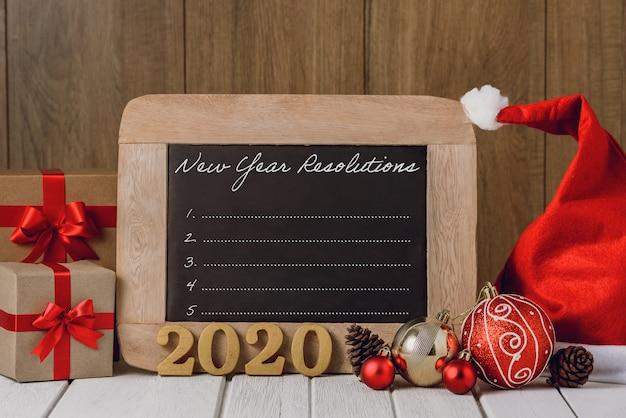 Texto de madera 2020 y adornos navideños y lista de resoluciones de año nuevo escrita en la pizarra sobre fondo de madera