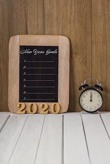 Texto de madera 2020 y lista de objetivos de año nuevo escrita en la pizarra con reloj despertador