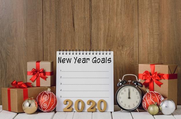 Texto de madera 2020 y reloj despertador con adornos navideños y lista de objetivos de año nuevo escrita en el cuaderno sobre fondo de madera