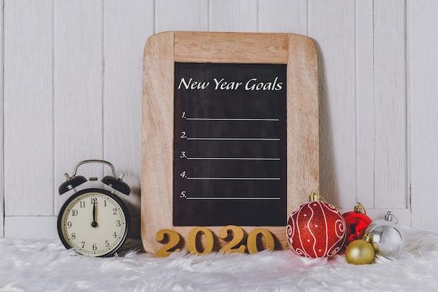 Texto de madera 2020 con reloj despertador con adornos navideños y lista de objetivos de año nuevo escrita en pizarra con pelaje blanco