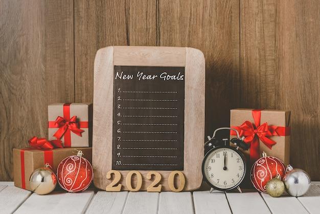 Texto de madera 2020 y reloj despertador con adornos navideños y lista de objetivos de año nuevo escrita en la pizarra sobre madera