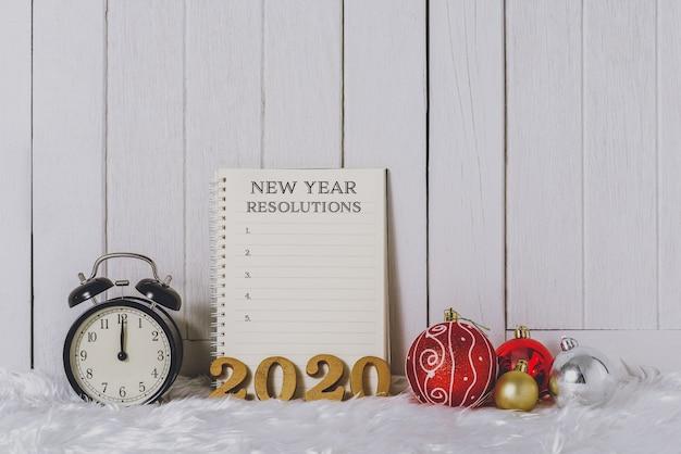 Texto de madera 2020 con reloj despertador con adornos navideños y lista de resoluciones de año nuevo escrita en un cuaderno con pelaje blanco