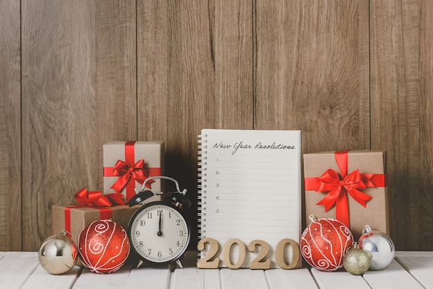 Texto de madera 2020 y reloj despertador con adornos navideños y lista de resoluciones de año nuevo escritas en el cuaderno sobre fondo de madera