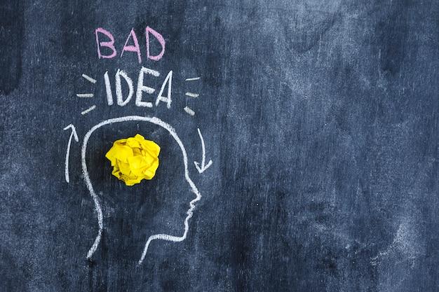 Texto de mala idea sobre la cabeza con papel amarillo arrugado en la cabeza dibujada en la pizarra