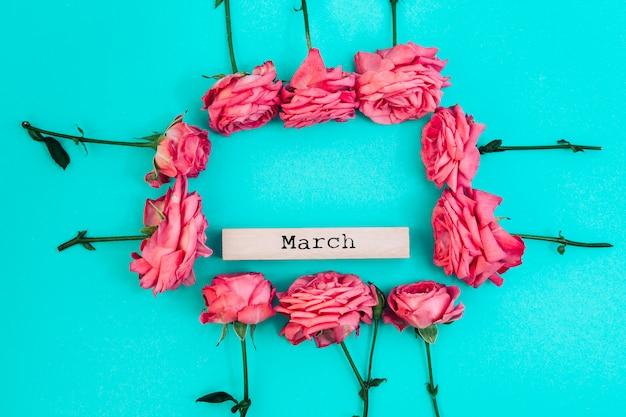 Texto de mayo dentro del marco de rosas frescas con fondo coloreado