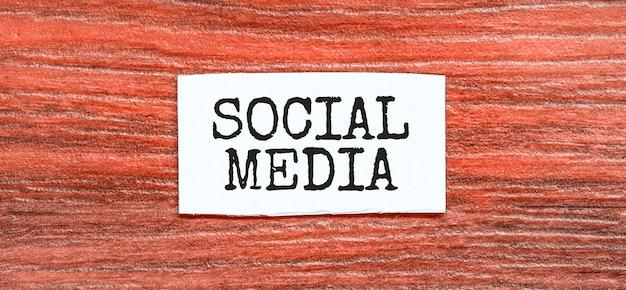 Texto de medios sociales en la hoja de papel en la madera roja