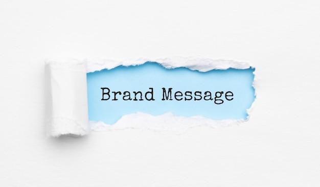 El texto mensaje de marca que aparece detrás de un papel amarillo rasgado