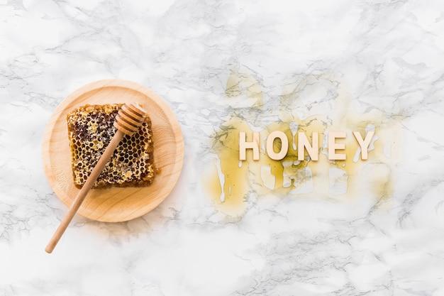 Texto de miel con panal y cazo en placa de madera sobre el fondo de mármol blanco