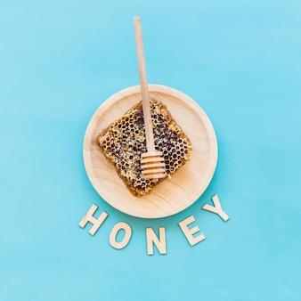 Texto de miel con panal y cucharón en placa de madera sobre el fondo azul