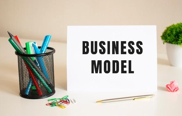El texto modelo de negocio está escrito en una hoja de papel doblada en blanco sobre la mesa. cerca hay bolígrafos y lápices.