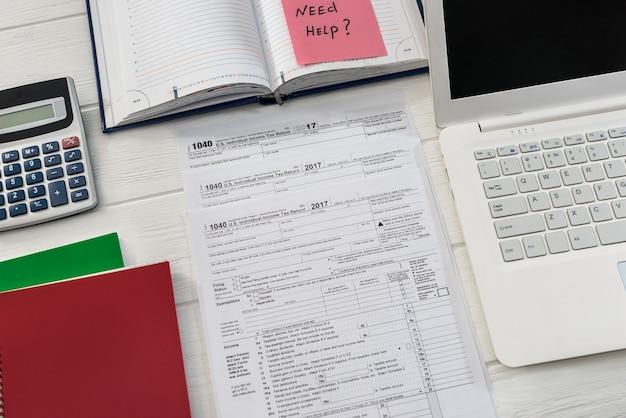 Texto de 'necesito ayuda' en el formulario 1040 y la computadora portátil