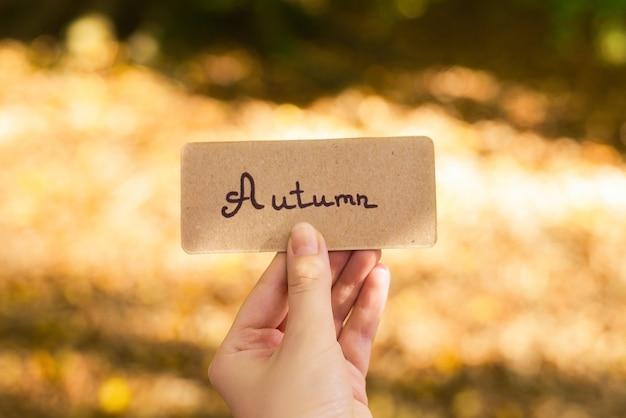 Texto de otoño en una tarjeta. tarjeta de explotación de niña en el parque de otoño en rayos de sol.
