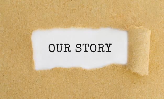 Texto our story que aparece detrás de papel marrón rasgado.