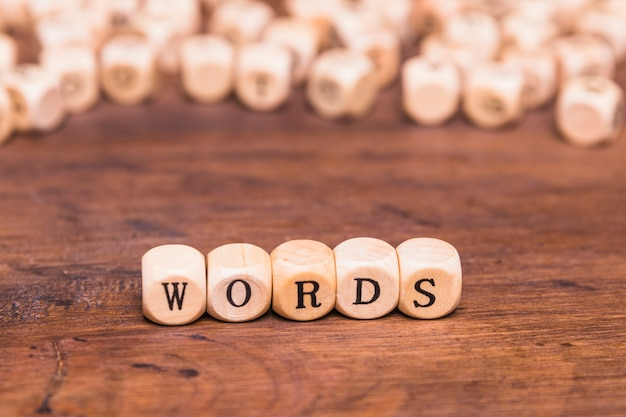 Texto de la palabra en dados de madera sobre el escritorio marrón