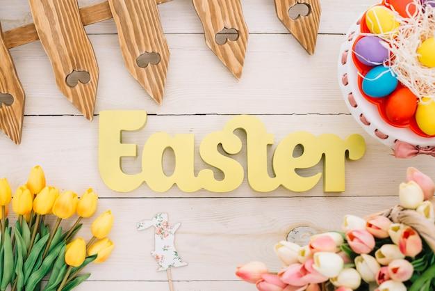 Texto de pascua con valla; apoyo de conejo; tulipanes y coloridos huevos de pascua en cakestand en escritorio