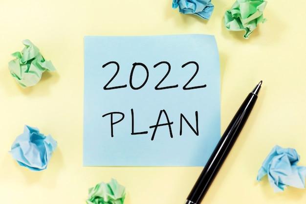 Texto plan 2022 en una pegatina azul, bolígrafo negro y trozos de papel sobre fondo amarillo.
