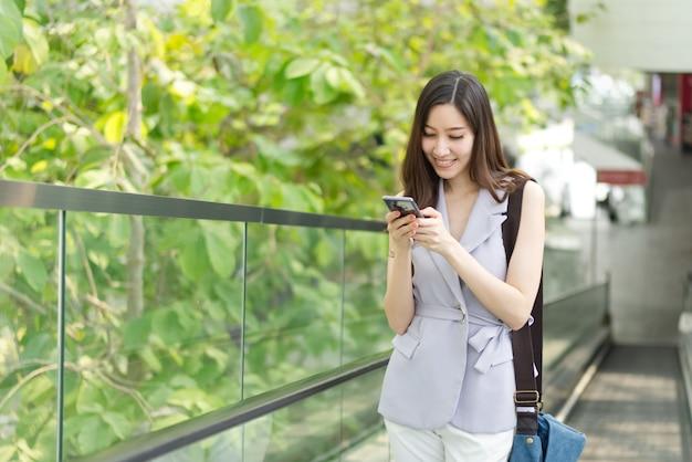 Texto que mecanografía asiático de la muchacha de oficina en el teléfono móvil que se coloca en el elevador en alameda de compras.