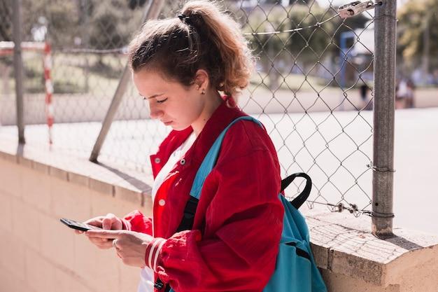 Texto que mecanografía de la chica joven en el smartphone cerca del sportsground